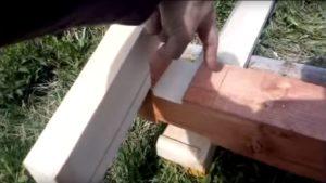 Пальцем указывается место крепления крыши к столбу