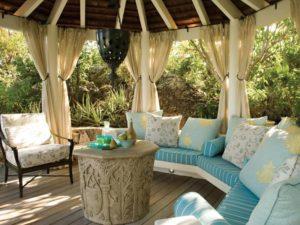 Круглая форма постройки с винтажными диванами, креслом и шторками